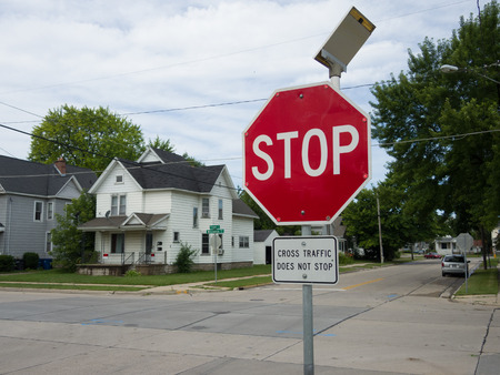 Solar powered LED flashing stop sign with a sign on the bottom saying Cross Traffic Does Not Stop.
