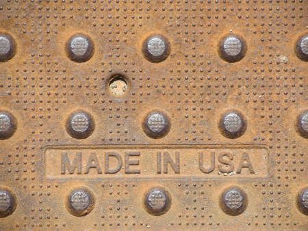 foundry: A heavy, rusty steel plate proudly stamped made in USA at the foundry.   It also has interesting dot patterns that provide traction for walking on. Stock Photo