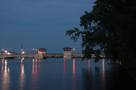 draw bridge: Just after dusk a drawbridge in Oshkosh, Wisconsin is illuminated by city lights. Stock Photo