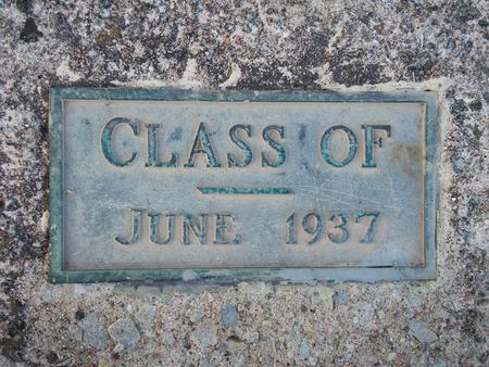 Een verweerde, groene, bronzen plaquette met veel patina viert de examenklas van 1936.