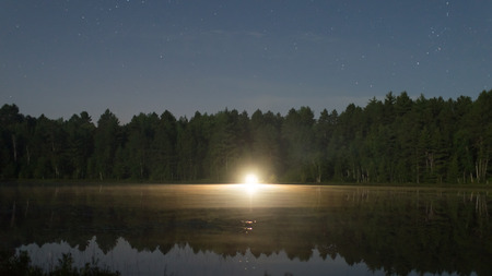 A light shines across the calm water of a lake directly at the camera.  In the night are stars