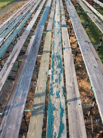 peeling paint: The old wooden bleachers offer peeling paint on the seats to the spectators at a football field.
