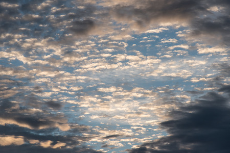 patchy: The lower clouds are dark, but they have parted revealing the bright patchy high clouds. Stock Photo