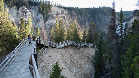 lower yellowstone falls: A mother and daugher walk hand in hand down a wooden boardwalk in the canyon to view the lower Yellowstone  Falls, at Yellowstone National Park.
