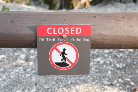 declaring: A sign posted on a fence declaring the area Closed Off Trail Travel Prohibited to protect both the environment, and hikers in the National Park.