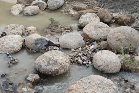 rock creek: Collection of shale rock nodules, many of which contain fossils in a creek bed in Badlands National Park, South Dakota. Stock Photo