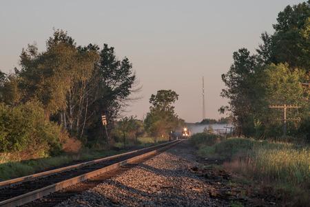 ferrocarril: Un tren de carga y sus faros emergen de un banco de niebla niebla en la ma�ana temprano y se viene abajo las v�as del ferrocarril.