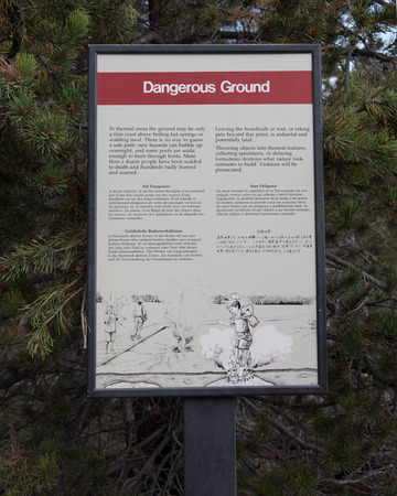 yellowstone: Dangerous Ground Sign at Yellowstone National Park warns visitors in several languages that it is dangerous  to walk of the boardwalk because they might fall into hot water.