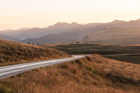 yellowstone: The mountain road through Yellowstone National Park is bathed in the golden glow of the early morning light.
