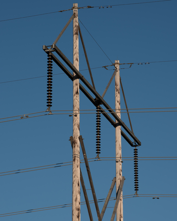 insulators: Electric power lines mounted on insulators and a tall wood power pole.  These wire transfer electrical energy to households and industry. Stock Photo