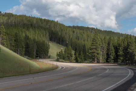 cutting through: Twisty, asphalt, mountain road, cutting through hills and forest in the Bighorn Mountains of Wyoming.
