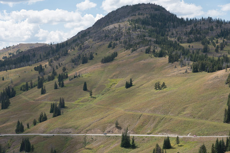 yellowstone: View of new and old road, with mountain covered both in forest and grass at Yellowstone National Park.