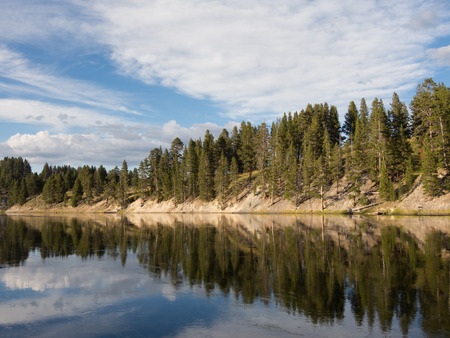 yellowstone: Scenic view of the mirror like water surface of the Yellowstone River and partly cloudy blue sky, Yellowstone National Park.