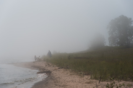 lost lake: Beach walkers disappear in the dense blanket of fog blowing of the waters of Lake Michigan.  Point Beach State Forest, Wisconsin.