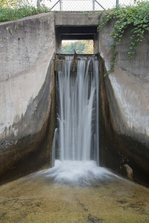 spillway: Waters streams over the spillway of a small concrete dam that blocks Hartman Creek and forms a small lake.