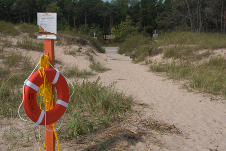 A life ring sits on a post on the beach ready to save swimmers from drowning. On Lake Michigan on the Wisconsin shore at Point Beach State Forest