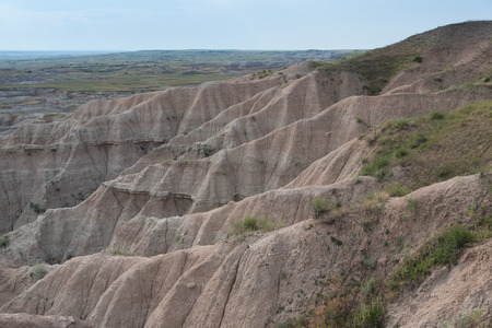 Steep badlands geologic features in the foreground with more rolling shortgrass prairie like ecosystem in the distant background.   South Dakota