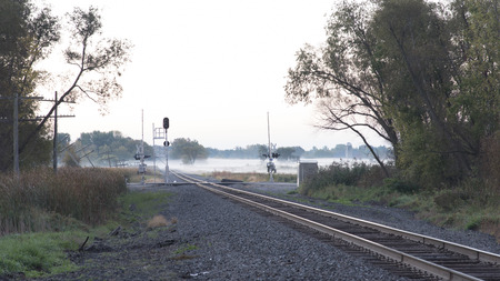 Fog over the wetlands and railroad tracks and crossing in the early morning.