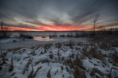 blazes: Sunset blazes away in orange and red over a lake and snow covered sedge wetland.