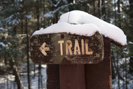 wooden trail sign: Wooden hiking trail sigh with arrow pointing the direction of the walking path.  The forest scene in winter shows snow on the ground and piled on the recreation sign.
