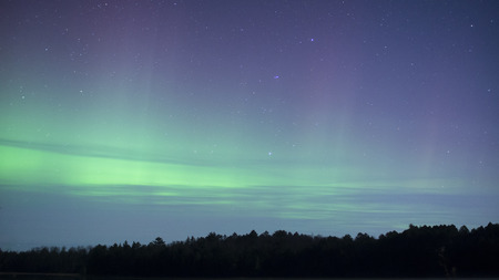 The colorful streaks of light of the Northern Lights, or the Aurora Borealis in the night sky.