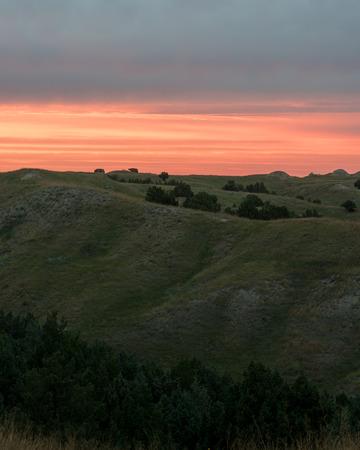 Oranje gloed van de zonsondergang over de glooiende shortgrass prairie grassen, en Rocky Mountain Jeneverbessen van de Great Plains in South Dakota. Stockfoto
