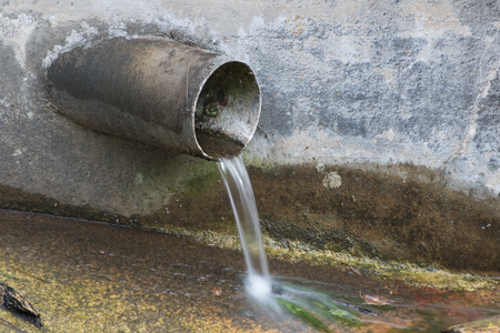 Drainage pipe protruding from a concrete wall into a stream.