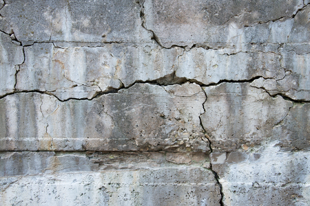 An old concrete wall has developed many cracks forming interesting patterns and designs.