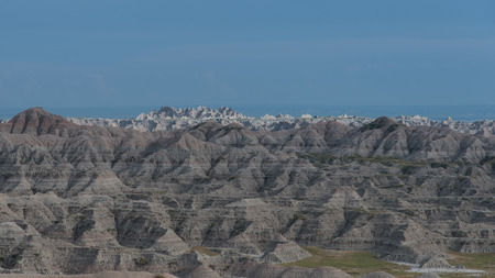 Light catches the distant rock soil geologic features at Badlands National Park, South Dakota.