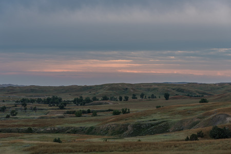 great plains: In the darkening evening colors still hang over the prairies of South Dakota at Badlands National Park.