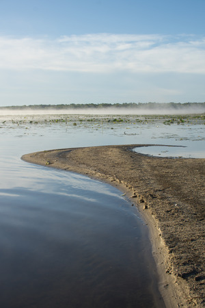 sandbar: Early in the morning, on a lake, a sandbar juts out into the water, pointing at low hanging bank of fog.