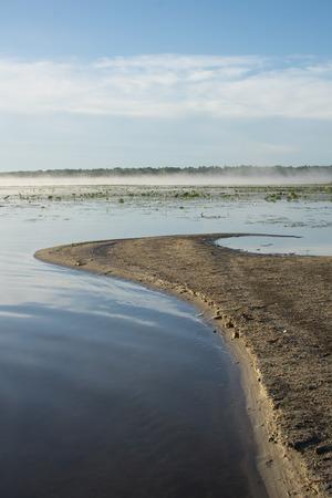 Vroeg in de ochtend, op een meer, een zandbank steekt uit in het water, wijzend op laaghangende mistbank. Stockfoto