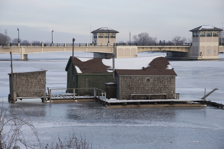 Fishing shack off of the shore of the Fox River in Oshkosh with the Wisconsin Street bridge in the background.