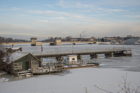 Fishing shack in ice with bridge and dock.