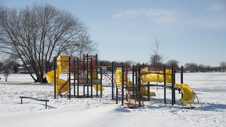 Playground equipment: slides, ladders, swings, etc.  in snow and snow drifts on a clear winter day.
