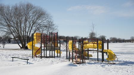 Speeltoestellen: dia's, ladders, schommels, enz. In de sneeuw en sneeuw drijft op een heldere winterse dag. Stockfoto