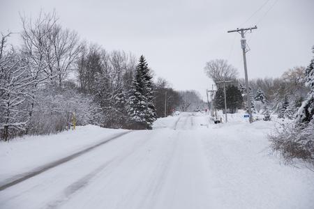 Een onlangs geploegd landweg na een sneeuwstorm. Sneeuw houdt zich aan de boomtakken in de winter scene. Stockfoto