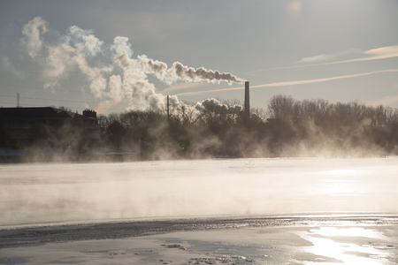 Steam rises off the water of the river and smoke and pollution puff out of a large coal smokestack on a cold winter day. Stock Photo