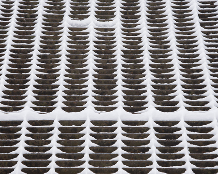 Snow even sticks to the thin metal grate on a catwalk over a dam. Stock Photo