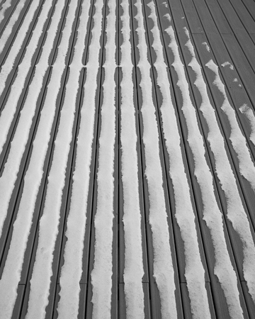 Patronen van de sneeuw op plastic terrasplanken.