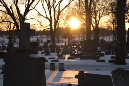 Zonsondergang in de winter over een besneeuwde begraafplaats met donkere grafstenen en bomen.
