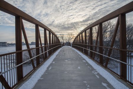 A walking bridge spans a river and leads to a snowy winter path.