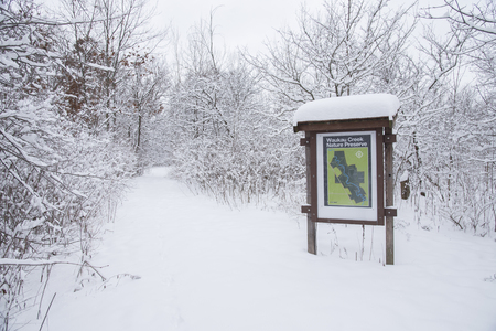 Waukau Creek Nature Preserve map and information sign in a snow-covered landscape.