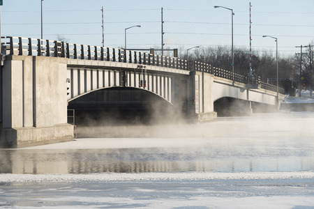 Drawbridge on a cold winter day.  There is on the river with open water and steam rising off the surface.