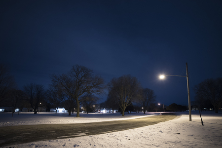 Streetlight illuminates the road and snow at night. Stock Photo