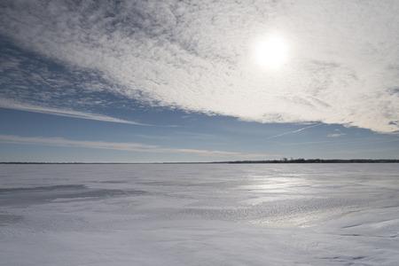 De verblindende winter zon gedeeltelijk verduisterd door een dunne laag van wolken, en gereflecteerd door de sneeuw en ijs op een meer. Stockfoto