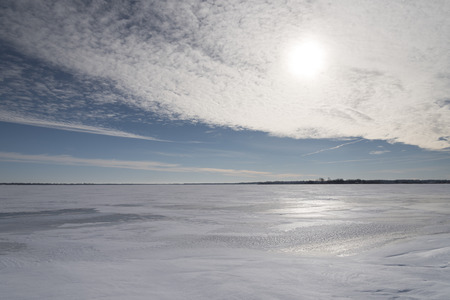 The blinding winter sun is partially obscured by a thin layer of clouds, and reflected by the snow and ice covering a lake. Stock Photo
