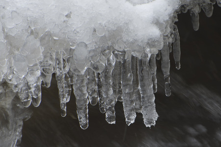 Icicles forming from the splashing water, and melting snow. Stock Photo