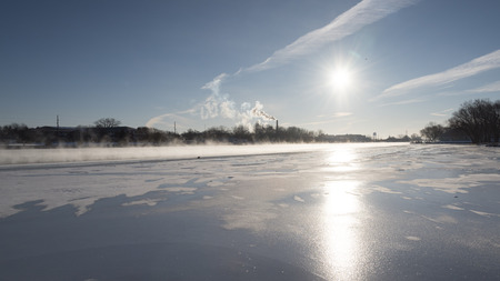 The frozen Fox River on a very cold day.  The low, blinding sun reflects off the smooth ice and steam rises off the open water of the river.