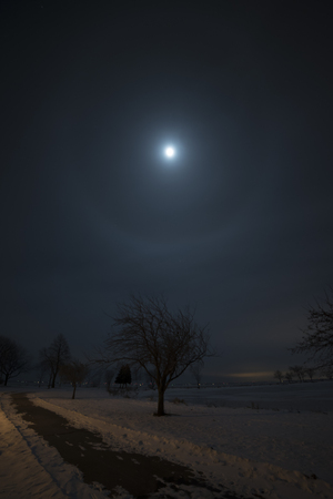 Moondog (moon halo) on a cold winter night, over a frozen Lake Winnebago.  The walking trail in the foreground is partially lit by the street lights of the City of Oshkosh. Stock Photo